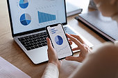 Close up of female employee analyze financial graphs