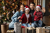 Portrait of smiling family with children pose near Christmas tree