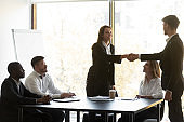 Boss greets corporate client express respect shaking hands starting meeting