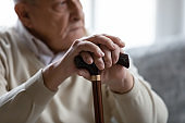 Close up focus on wrinkled male hands leaning at wooden stick.