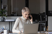 Smiling businesswoman work on computer talking on cell
