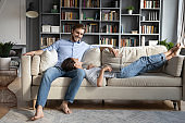 Happy couple relax on couch using laptop