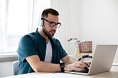 Male employee in wireless headphones work on laptop
