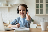 Adorable little european kid online education courses at home.