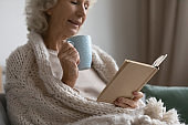 Mature woman relaxing on sofa drinking tea reading a book