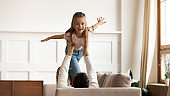 Overjoyed little girl playing with loving dad at home