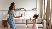 Young babysitter dancing to music with daughter at home.