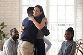 Happy man and woman hug showing support at therapy session