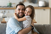 Portrait of happy young dad and daughter hugging