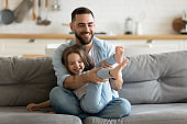 Smiling father playing relaxing with little daughter