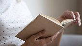 Close up female wrinkled hands holding paper book.