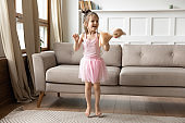 Energetic small child girl dancing alone in living room.