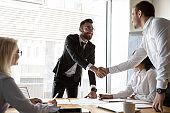 Smiling businessmen handshake greeting at team office meeting