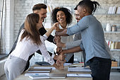 Smiling diverse employees stack fists at corporate meeting, celebrating success.