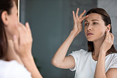 Anxious woman looking in mirror, touching forehead, confused about wrinkles