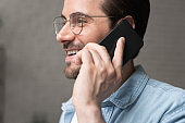 Happy handsome 30s man in eyewear holding mobile call conversation.