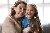 Portrait of smiling mature woman posing with little granddaughter