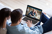 Couple communicating with elderly parents using laptop and videocall app