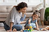 Laughing mother and little daughter playing colorful wooden blocks