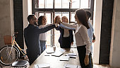 Excited diverse business people giving high five at corporate meeting