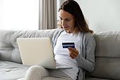 Positive woman paying online with credit card, using laptop