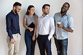 Overjoyed multiethnic millennial employees laugh posing together