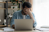 Unhappy man feel distressed reading bad email letter
