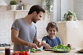 Young dad and little son preparing salad together
