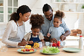 Loving biracial parents cooks in kitchen with small kids