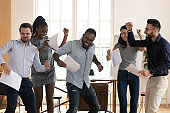 Overjoyed multiethnic employees dancing at workplace celebrating work success