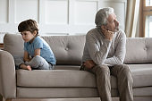 Upset mature grandfather and little grandson avoid talking after fight