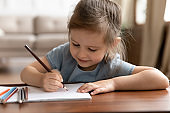 Cute little preschool child girl drawing pictures with colored pencils.