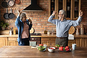 Excited healthy senior couple dance cooking together