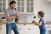 Happy dad and small son have fun singing at home