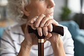 Disabled middle aged elder woman holding wooden stick, close up.