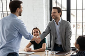 Happy male colleagues handshake closing deal in office