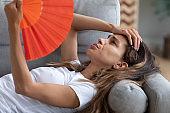 Stressed woman touching forehead, suffering from heat, waving fan