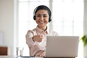 Happy indian hr manager wearing headphones, pointing finger at camera.