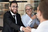 Smiling multiracial business partners handshake closing deal