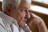 Head shot unhappy thoughtful older man lost in thoughts