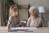 Happy mature grandmother and little granddaughter drawing together