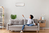 Happy african woman sitting on sofa switching on air conditioner