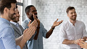 Excited diverse employees applauding, celebrating business achievement, success