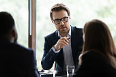 Confident businessman head meeting with colleagues in office boardroom