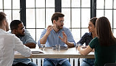 Diverse employees listening to confident business coach at meeting