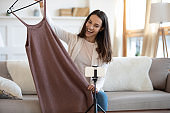 Smiling young woman shoot clothing unpacking video