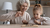 Happy mature grandmother and little granddaughter play chess