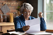 Happy mature woman excited with good news in paper letter