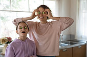 Portrait of happy mom and teen daughter have fun cooking