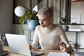 Focused businesswoman working on research sit at desk use laptop